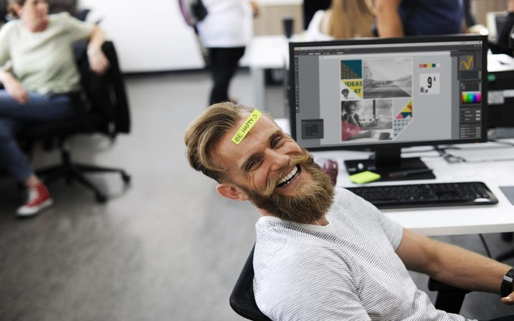 Happy employee by his desk