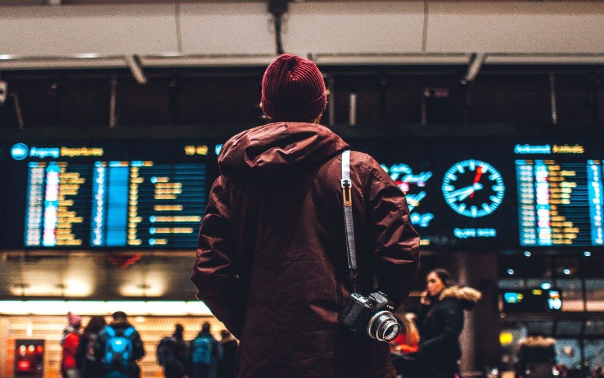 Man standing in front of the departures board at an airport